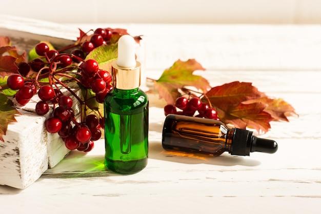 Bottiglie cosmetiche con prodotto per la cura della pelle antietà sullo sfondo di una scatola bianca con un ramo di viburno e bacche mature.