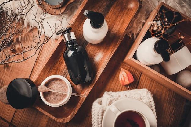 Flaconi per la cosmetica con cosmetici per la cura del corpo su un tavolo di legno.