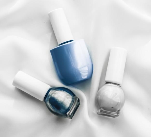 Salone di branding cosmetico e concetto glamour bottiglie di smalto per unghie su sfondo di seta prodotti per manicure francese e cosmetici per il trucco smalto per il marchio di bellezza di lusso e design artistico flatlay per le vacanze