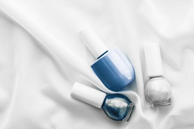 Salone di branding cosmetico e bottiglie di smalto per il concetto di glamour su sfondo di seta french manicure ...