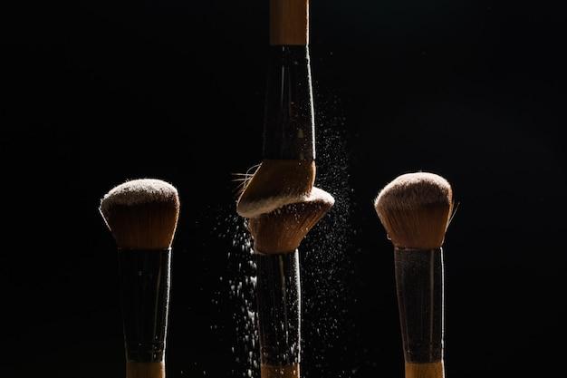 Pennello cosmetico con polvere cosmetica da spalmare su sfondo nero