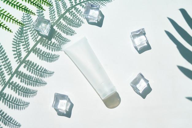 Bolla cosmetica e ghiaccio su uno sfondo di belle ombre di palme. modello