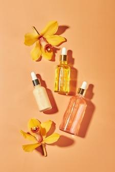 Prodotti cosmetici per la cura in flaconi di vetro con sieri di fiori di orchidea crema gel oli concetto per il viso ...