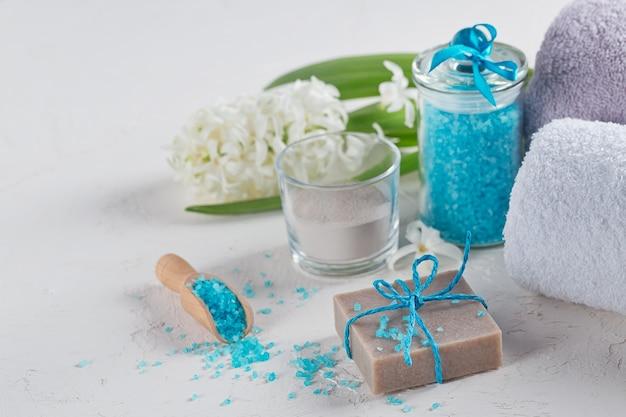 Polvere di argilla cosmetica, sapone di argilla fatto in casa e sale marino da bagno blu su sfondo bianco. cura del viso, cura del corpo e concetto di spa.