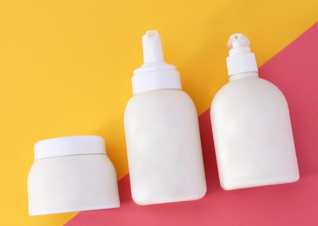 Contenitori cosmetici isolati su sfondo colorato