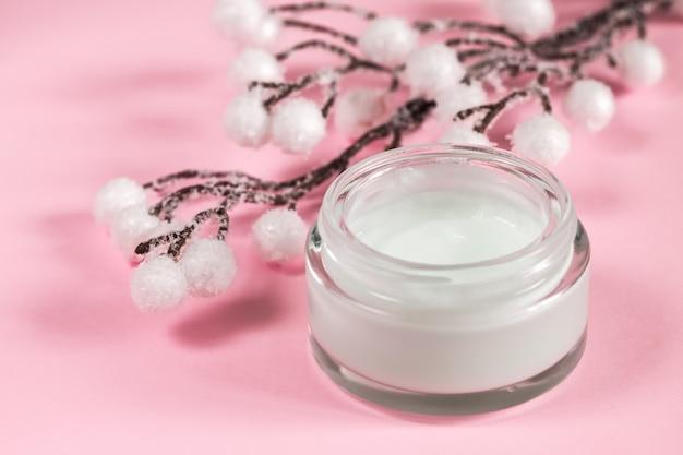 Contenitore cosmetico crema su sfondo rosa con fiori.