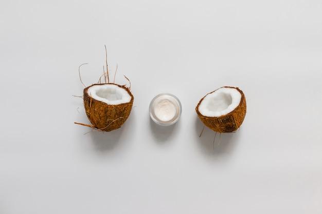 Crema cosmetica per viso o corpo in un barattolo di vetro con mezza noce di cocco su uno sfondo grigio, vista dall'alto, piatto disteso
