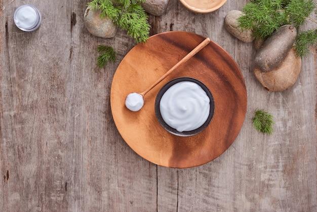 Crema cosmetica e foglie di lavanda fresche sul fondo di legno bianco della tavola