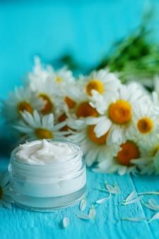 Crema cosmetica con fiori di camomilla o un corpo e viso sul tavolo di legno blu