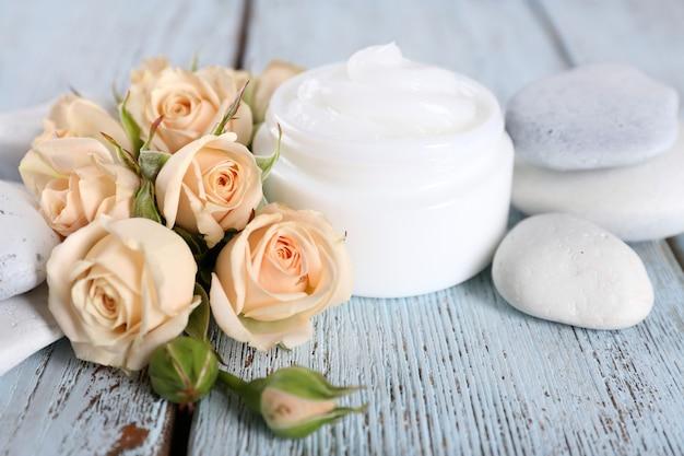 Crema cosmetica con fiori e pietre spa su legno