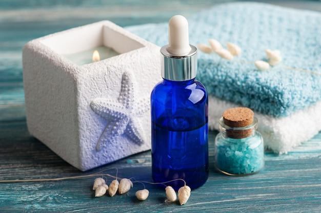 Olio essenziale cosmetico su fondo in legno. spa biologica naturale con packaging ecologico e sale marino