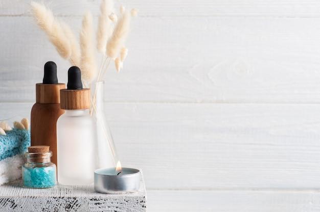 Olio essenziale cosmetico su fondo in legno. spa biologica naturale con confezione ecologica con spazio di copia