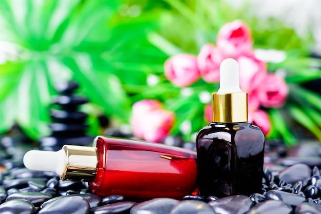 Bottiglia di vetro cosmetica per oli essenziali su pietra nera
