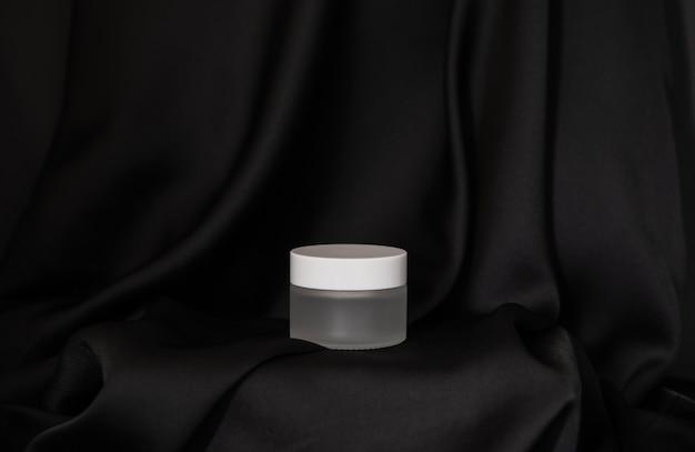 Il barattolo cosmetico si trova su uno sfondo di seta nera