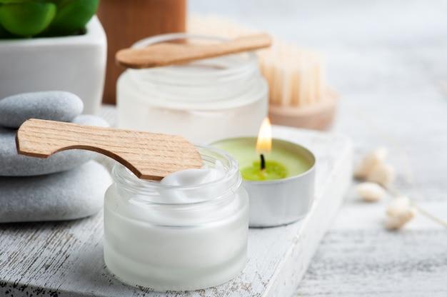 Vaso cosmetico con crema, lozione idratante per il corpo o maschera su fondo in legno. spa biologica naturale con packaging ecologico