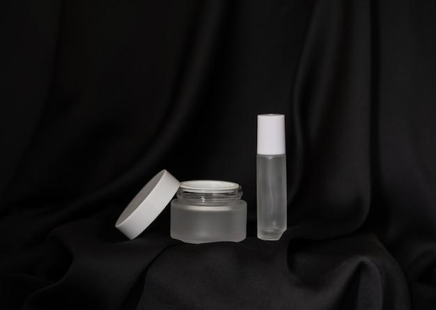 Vaso cosmetico con coperchio aperto e spray cosmetico su sfondo di tessuto nero