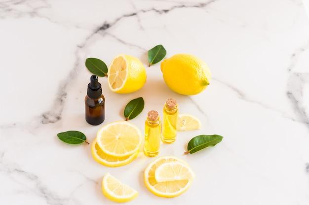 Olio di limone cosmetico e olio essenziale di agrumi su un tavolo di marmo. frutti di limone fresco e foglie di melisa. cosmetici della natura in bottiglie di vetro.