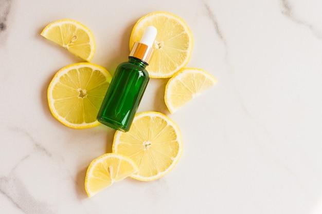 Olio di limone cosmetico o olio essenziale in una bottiglia con una pipetta di vetro verde sullo sfondo di fette di limone e un tavolo di marmo.