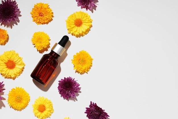 Bottiglia di olio cosmetico su sfondo di boccioli floreali