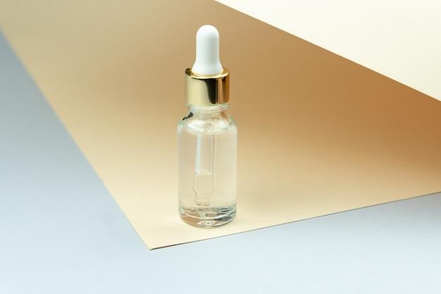 Bottiglia di olio cosmetico con contagocce della pipetta in piedi su sfondo marrone chiaro. concetto di cura della pelle.