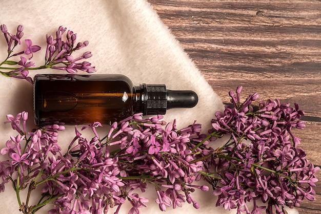 L'olio cosmetico per la cura del viso e del corpo giace su un asciugamano bianco. con fiori lilla. su uno sfondo di legno.