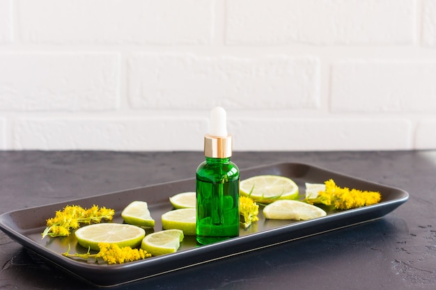Olio cosmetico da agrumi frkt in una bottiglia con una pipetta su uno sfondo nero di fronte a un muro di mattoni bianchi.