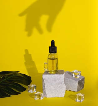 Olio cosmetico per capelli o viso in una bottiglia di vetro con una pipetta. cura del corpo, spa. colori di tendenza, ombre e cubetti di ghiaccio.