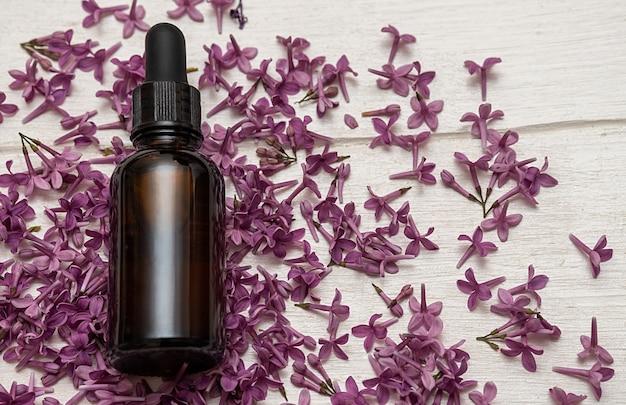 Olio cosmetico in fiori lilla. cosmetici per la cura della pelle del corpo e del viso. su sfondo bianco.