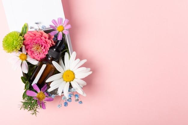Olio cosmetico o profumo o farmaco in vetro marrone con pipetta e fiori