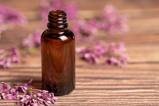 L'olio cosmetico si trova su uno sfondo di legno. fiori di porpora lilla giacciono sul tavolo.