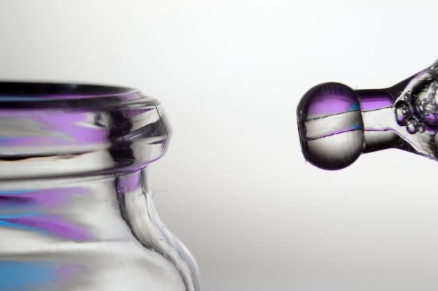 Una pipetta cosmetica con un liquido raccolto in essa da una bottiglia. avvicinamento.