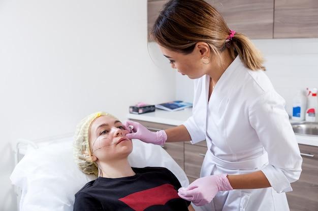 Procedura cosmetica per la correzione degli zigomi con l'aiuto di iniezioni di botox. medico asiatico della donna perfora nello zigomo di una giovane donna