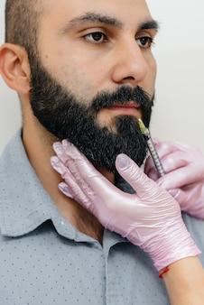 Procedura cosmetica per l'aumento delle labbra e la rimozione delle rughe per un uomo barbuto. cosmetologia.