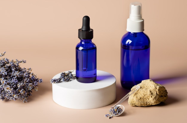Prodotto cosmetico in bottiglie di vetro blu su podio bianco con lavanda essiccata su fondo corallo chiaro