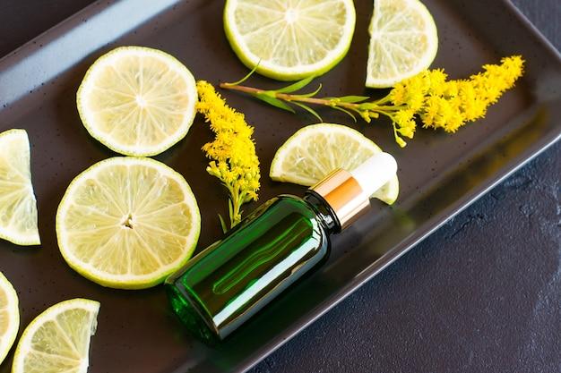 Prodotto cosmetico per la cura della pelle del viso in una bottiglia con una pipetta sullo sfondo di un piatto di ceramica con fette di limone.