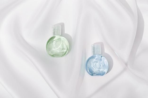 Prodotto cosmetico in bottiglia di plastica trasparente con belle ombre sulla trama del panno di seta bianca