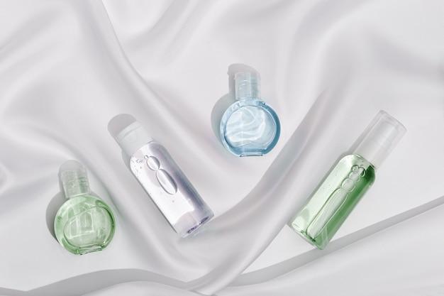 Prodotto cosmetico in bottiglia di plastica trasparente con bellissime ombre su tessuto di seta bianca