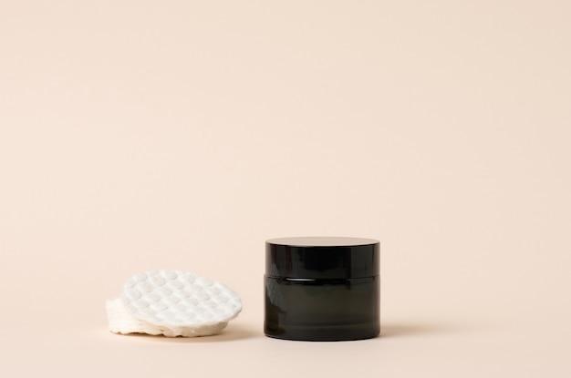 Prodotti cosmetici in un barattolo di vetro nero con coperchio e batuffolo di cotone bianco. vuoto per prodotti di branding, crema idratante su fondo beige