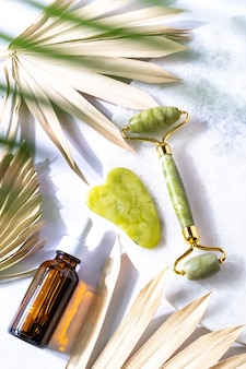 Prodotti cosmetici bottiglia olio viso rullo e massaggiatore gua sha vista dall'alto spa relax