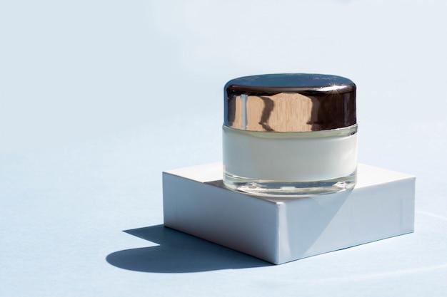 Prodotti cosmetici per il viso. vasetto di crema, maschera per il viso su una scatola bianca. beauty blogger, procedure salone concetto. minimalismo.