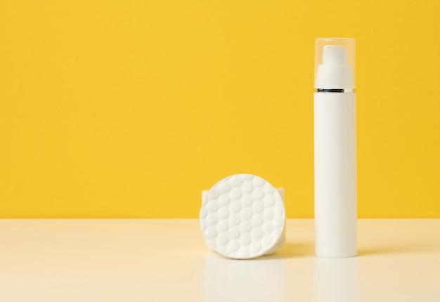 Prodotti cosmetici in una bottiglia di plastica bianca e un batuffolo di cotone bianco. vuoto per prodotti di branding, crema idratante su sfondo giallo