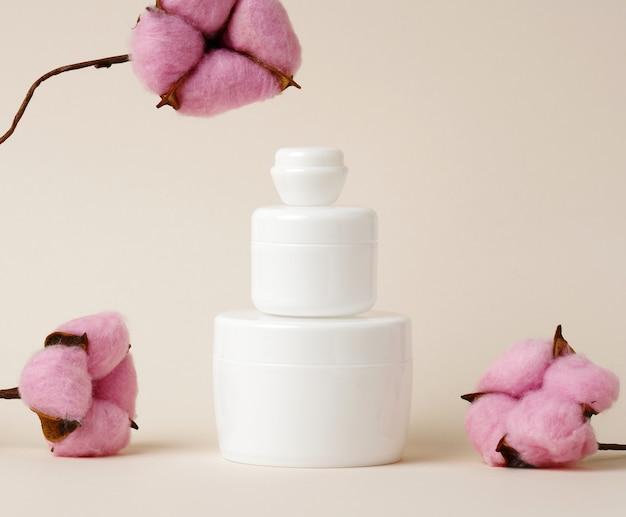 Prodotti cosmetici in un barattolo di plastica bianca con coperchio. vuoto per prodotti di branding, crema idratante su fondo beige, mock up