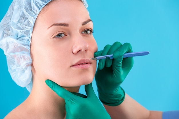 Chirurgo estetico che esamina cliente femminile in ufficio. medico che controlla il viso della donna, la palpebra prima della chirurgia plastica, la blefaroplastica. mani del chirurgo o dell'estetista che toccano il fronte della donna. rinoplastica