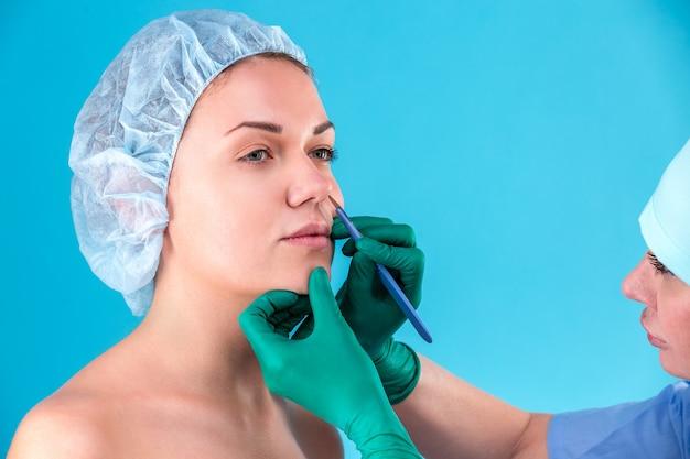 Chirurgo estetico esaminando cliente femminile in ufficio. medico che controlla il viso della donna, la palpebra prima della chirurgia plastica, la blefaroplastica. mani del chirurgo o dell'estetista che toccano il fronte della donna. rinoplastica