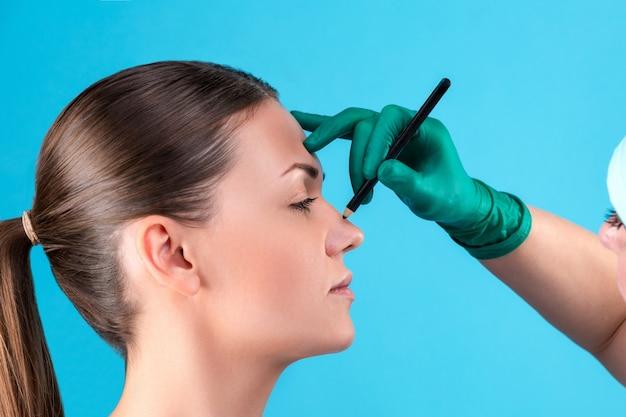 Chirurgo estetico che esamina cliente femminile in ufficio. il medico traccia le linee con un pennarello, la palpebra prima della chirurgia plastica, la blefaroplastica. mani della donna dell'estetista o del chirurgo che toccano il fronte della donna. rinoplastica