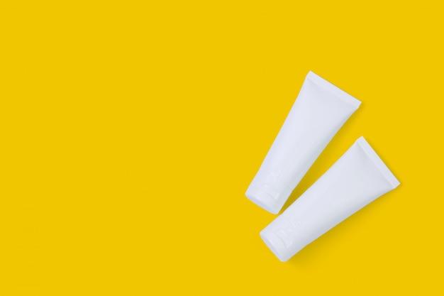 Tubo cosmetico isolato su sfondo giallo.