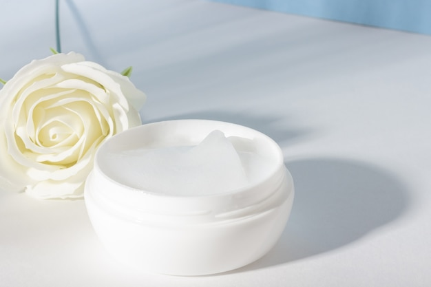 Vaso cosmetico bianco aperto di crema viso idratante. contenitore di plastica con crema, lozione, maschera per il viso. il concetto di cosmetologia ecologica e organica.