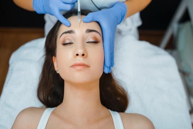 Estetista in guanti dà iniezioni di botox viso al paziente femminile sul tavolo di trattamento.