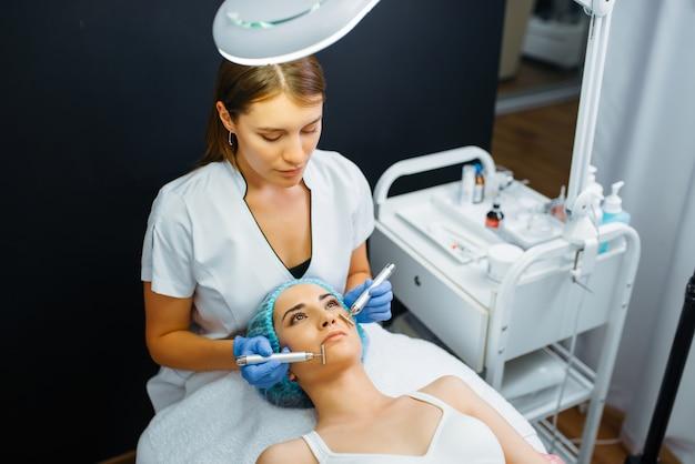 Estetista leviga il viso del paziente femminile dopo iniezioni di botox.