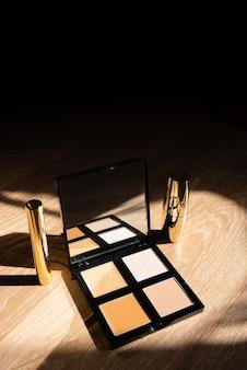 Cosmetici. ombretto e rossetto in confezione dorata su fondo in legno. formato verticale